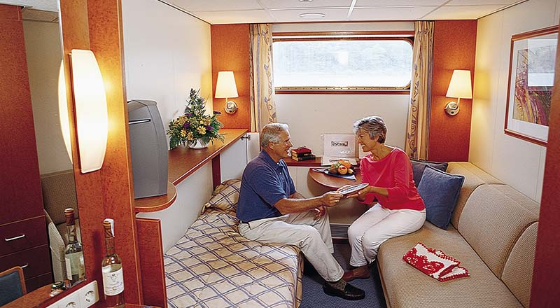Couple chatting inside standard stateroom