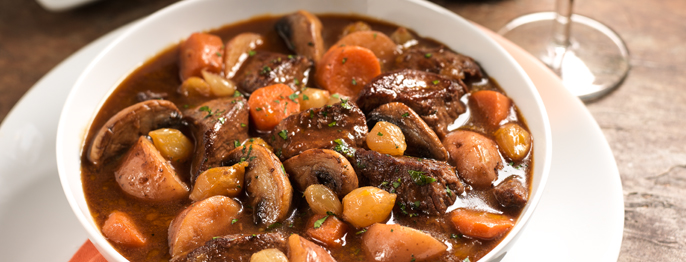 Beef, mushrooms, carrots, and other vegetables in a brown liquid served in a white bowl.