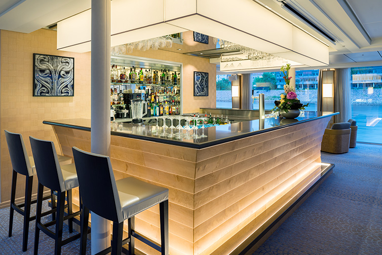 Golden-lit bar with a dark black bar-top and sparkling glassware on board Viking Beyla.