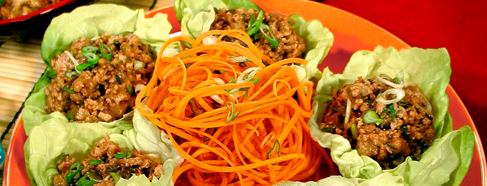 Lettuce served shaped into cups, containing ground chicken and chives, surrounding shaved carrots.