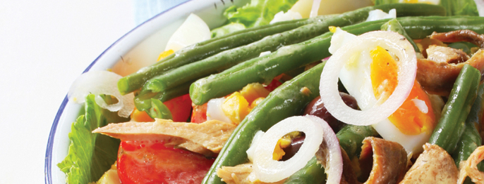 A cropped shot of green beans, tomatoes, croutons, and lettuce in a white bowl rimmed with blue.