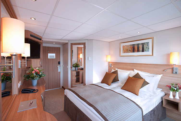 Interior of a stateroom bedroom on a Viking Prestige Deluxe room.