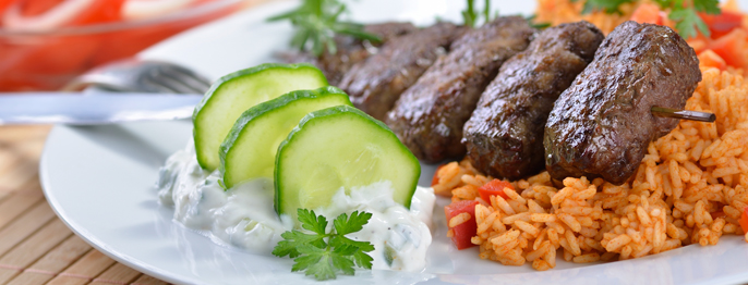 A plate of food containing skewered meat, rice, tzatziki dip, and sliced cucumbers.