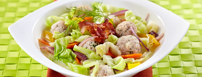 Cabbage and meatballs served with red and yellow vegetables on a bright green, woven placemat.