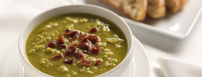 Chunky green split pea soup served with crumbled bacon in a white porcelain dish.