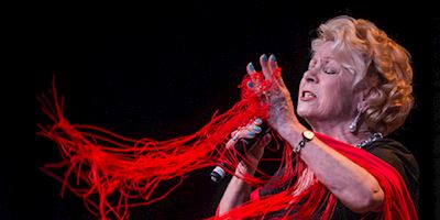 A woman with red fringe singing emotionally into a microphone.