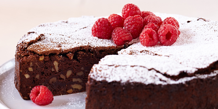 Flourless chocolate cake studded with nuts, generously sprinkled with powdered sugar and topped with fresh raspberries.