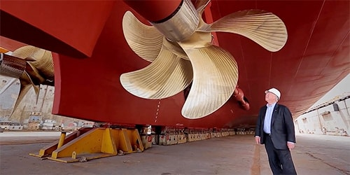 Tor Hagen standing under a huge gold rotar underneath a Viking Ocean Ship.