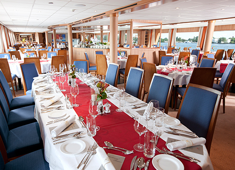 Set tables in the restaurant of a Viking river ship