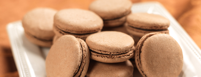 A plate full of chocolate macarons, a small round sandwich cookie with a crispy outer shell.