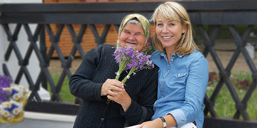 Karine Hagen and Nadya, a grandmotherly woman holding boquets of purple flowers.