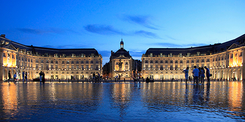 A palace in Bordeaux lit from the night sky and twinkling water.