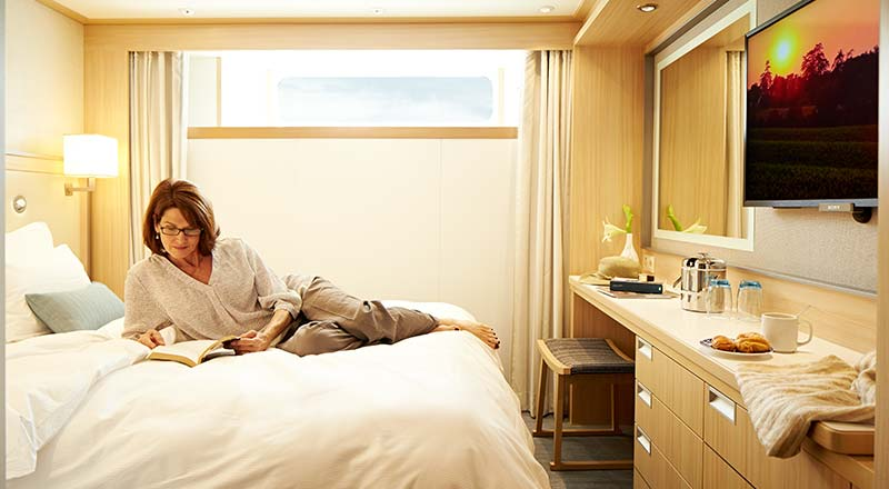 A woman lounging on a Viking Standard Stateroom bed, reading a book.