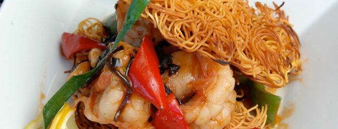 A cropped shot of shrimp, red peppers, crispy brown noodles, and a few colorful vegetables on white plate.