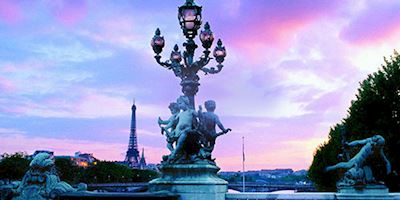 Pink and purple sky over a cherub-lined streetlamp in Paris.