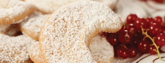 A pile of pale cookies sprinkled generously with powdered sugar, served next to bright red berries.