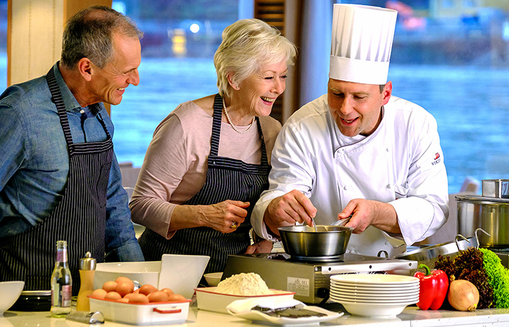A chef teaching a cooking class to two people