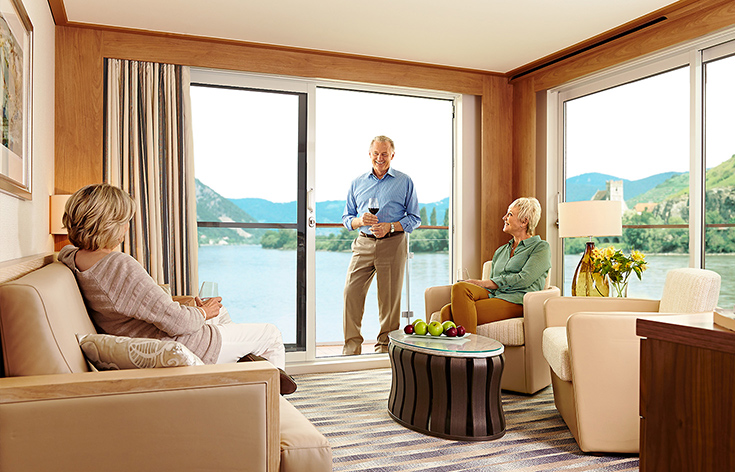 Three people socializing in a living area of a Viking stateroom