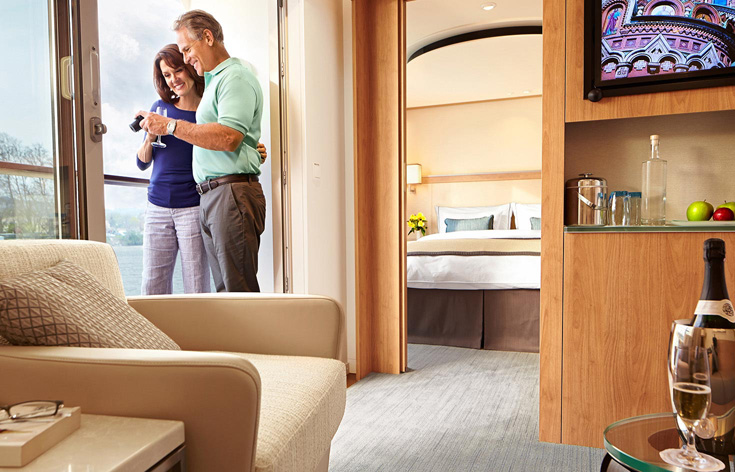 A couple viewing photos in a Viking stateroom